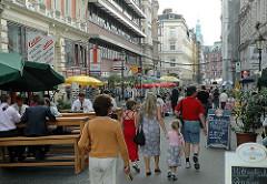 Passanten und Strassenrestaurant in den Colonnaden. Tische und Stühle stehen auf der Strasse.