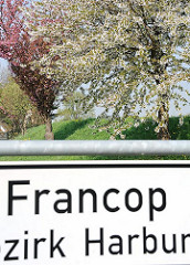 Stadtteilschild Francop, Bezirk Harburg - blühende Bäume auf dem Deich.