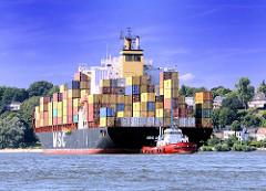 Ein Containerschiff läuft aus dem Hamburger Hafen aus - ein Hafenschlepper dirigiert das Frachtschiff in die Fahrrinne der Elbe.