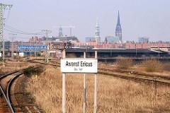 """Güterzugstrecke  beim Oberhafenkanal - Schild """"Awanst Ericus"""" Ausweichanschlussstelle / im Hintergrund die Kirchentürme der Hansestadt Hamburg."""
