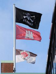 Hamburg Flagge und Fahnen des Fussballclubs FC St. Pauli am Millerntorstadtion.