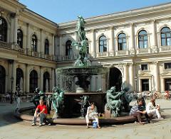 Innenhof des Hamburger Rathauses - Hygieia Brunnen mit Bronzefiguren- Hamburgtouristen sitzen am Rand des Brunnens in der Sonne.