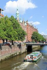 """Eine Barkasse der Hamburger Hafenrundfahrt fährt im St. Annenfleet Richtung Holländischem Brookfleet - rechts der Giebelturm des """"Speicherstadt-Rathauses"""" in dem die HHLA ihren Sitz hat."""