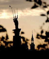 Bronzeplastik - Drei Männer im Boot - Künstler Edwin Scharff - im Hintergrund der Kirchturm der Dreieinigkeitskirche in Hamburg St. Georg.