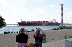 Containerschiff auf der Elbe - Elbstrand mit Leuchtturm von Hamburg Blankenese - ein Paar fotografiert das riesige Frachtschiff.