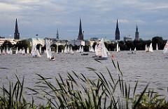 Blick vom Uhlenhorster Alsterufer auf die Aussenalster und das Panorama Hamburgs mit den vielen Kirchtürmen über den Dächern der Hansestadt.