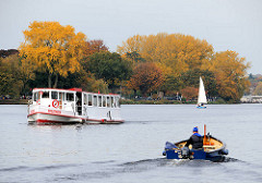 Herbstliches Hamburg - goldener Herbst in der Hansestadt - bunte Herbstbäume am Ufer der Aussenalster von Hamburg Rotherbaum - Alsterschiff Bredenbek - Motorboot auf dem Wasser.