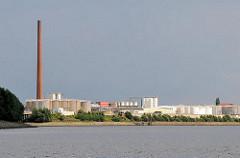 Tanklager und hoher Ziegelschornstein am Ufer des Reiherstiegs in Hamburg Wilhelmsburg.