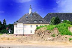 Erdberge auf der Baustelle Jenfelder Au - Hauptgebäude mit Uhrenturm der Lettow Vorbeckkasern.