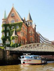 Historisches Speichergebäude in der Hamburger Speicherstadt - an der Fassade rankt Kletterwein. Die Barkasse der Hafenrundfahrt hat einen flachen Aufbau, damit sie die Brücken passieren kann.