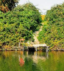 Ruheplatz am Ufer des Billbrookanals - Stuhl am Wasser des Industriekanals im Billbrooker Gewerbegebiet der Hansestadt Hambrug.