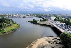 Blick über die Norderelbbrücken - rechts die Einfahrt zum Billhafen + Oberhafenkanal; lks. die Spitze des Elbparks Entenwerder und dem Haken. Im Hintergrund Häuser und Industrieanlagen auf der Veddel.