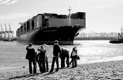 Der Containerfrachter CMA CGM CARMEN läuft in den Hamburger Hafen ein - das Frachtschiff wendet auf der Elbe; Zuschauer am Elbstrand bei der Strandperle in Hamburg Othmarschen.