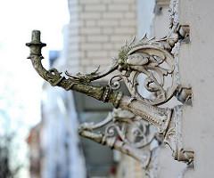 Schmiedeeiserne Reste historischer Lampen an einer Hauswand.