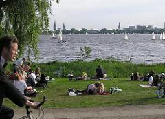 Hamburgs Grünanlagen - Alsterpark an der Aussenalster von Hamburg Uhlenhorst - Liegewiese an der Alster - HamburgerInnen liegen im Gras in der Sonne.