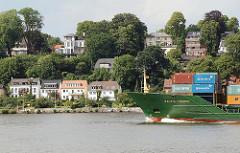 Elbufer von Hamburg Othmarschen - Wohnhäuser an der Elbe - Containerfeeder mit Fracht in Fahrt.