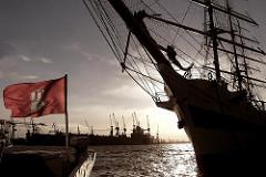 Hamburger Sonnenuntergang an den St. Pauli Landungsbrücken; Hamburger Flagge im Wind - Bugspriet eines Segelschiffs - Grossseglers, Masten