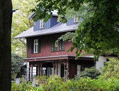 Villa mit holzverkleideter Fassade und Wintergarten im Niendorfer Gehege - Haus im Wald zwischen Bäumen.