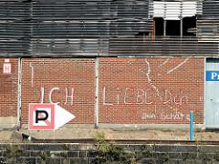 """Graffiti an der Wand des Lagerschuppens am Versmannkai: """"Ich liebe dich, dein Schatz""""; im Vordergrund die Kaimauer und ein Hafenzeichen """"Anlegen verboten""""."""