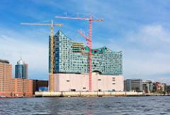 Baustelle der Elbphilharmonie in der Hafencity - Hamburgs größte Baustelle; Baukräne, blauer Himmel - Sonne, Schleierwolken.