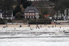 Spaziergänger im Winter im Eis am Ufer der Elbe - Strandspaziergang im winterlichen Hamburg.