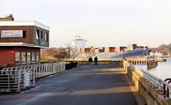 Hochwasserschutzanlage Hamburg Finkenwerder - Fischrestaurant mit Blick auf die Elbe - Containerschiff in Fahrt Richtung Hafen Hamburg.