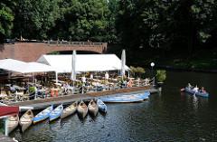 Café und Restaurant auf dem Golbekkanal am Rande des Hamburger Stadtparks - Kanus einer Kanuvermietung.