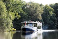 Ausflugsschiff der Bergedorfer Schifffahrtslinie auf der Doveelbe vor Hamburg Neuengamme - Bäume stehen bis dicht an das Ufer des Flusse..