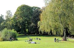Ein sonniger Tag in Hamburg Eppendorf - Menschen liegen in der Sonne auf der Liegewiese oder spielen Ball.
