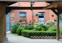 Hauseingang eines Wohnhauses in Hamburg Neuallermöhe - Buchsbaum und blühende Pflanzen.