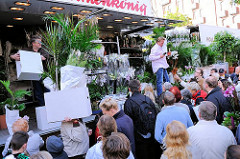 Marktstand zum Verkauf von Pflanzen - die als Schnäppchen erstanden Grünpflanzen werden von den KäuferInnen im Karton weggetragen.
