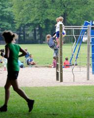 Kinderspielplatz - Volkspark in Hamburg Bahrenfeld; Klettergerüst mit Kindern - eine Joggerin läuft über den Rasen der grossen Wiese.