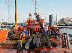 Harburger Binnenhafen - entfernen von Holzdalben, Holzpfählen aus dem Hafenbecken - Arbeitsboot.