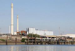 Bilder Wilhelmsburger Industriearchitektur - Silos und Schornsteine; am Ufer des Reiherstieg ein Anlegeplatz für Tankschiffe und die dazugehörigen Verladevorrichtungen.