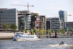 Moderne Wohnhäuser am Kai des Grasbrookhafens in der Hamburger Hafencity - ein Fahrgastschiff fährt Richtung St. Pauli Landungsbrücken.