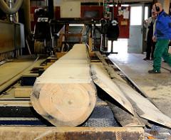 Die ersten Bretter sind mit der Blockbandsäge von dem Baumstamm gesägt und liegen abgelängt neben der Stammware - Bilder von der Zuschneidung von Holzbohlen für den Bau des Vierländer Ewers in Hamburg Bergedorf.