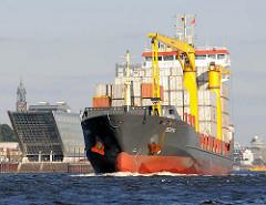 Der Containerfeeder BERTA läuft aus dem Hamburger Hafen aus - das Frachtschiff hat eine Länge von 107m und kann 645 Standartcontainer TEU transportieren - im Hintergrund ein Bürogebäude in Hamburg Altona Altstadt und die Spitze des Kirchturms vom Mic