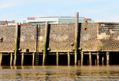 Kaimauer  im Hamburger Baakenhafen / Versmannkai bei Ebbe; die Kaianlage ist auf Holzstämmen gegründet - Streichdalben schützen die Wand / Schiffe beim Anlegen. Eine Eisenleiter führt zum Wasser.