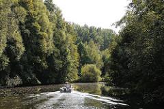 Sportboot auf der Bille - dicht bewachsenes Flussufer in Hamburg Billbrook.