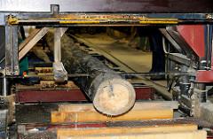 Eine Blockbandsäge trennt vom Stammholz ein Brett ab - Arbeiten für den Bau des Vierländer Gemüseewers in Hamburg Bergedorf.