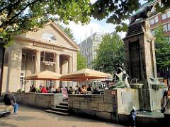Mönckebrunnen und sogen. Kulturcafe - Gäste sitzen in der Sonne an der Mönckebergstrasse im Stadtteil Hamburg Altstadt.