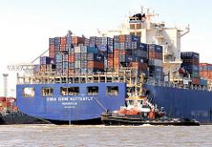 Hoch beladenes Heck des Containerfrachters CMA CGM BUTTERFLY im Waltershofer Hafen von Hamburg - ein Hafenschlepper zieht das 43m breite Containerschiff von der Kaimauer ab.