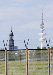 Zollzaun am Klütjenfelder Hauptdeich - hinter dem Stacheldraht der Hamburger Fernsehturm und der Kirchturm der St. Michaeliskirche.