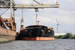 Massengutfrachter in der Dradenau - die Ladung wird über einen Kran gelöscht.