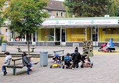 Geschäfte und spielende Kinder auf einem Platz am Alten Teichweg - Bilder aus dem Hamburger Stadtteil Dulsberg.
