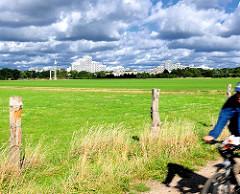 Wiese mit Zaun - im Hintergrund Hochhäuser der Grosssiedlung Osdorfer Born - ein Radfahrer fährt auf einem Feldweg - Hamburgbilder aus den Stadtteilen - Fotos aus Osdorf.