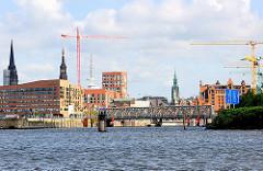 Blick von der Norderelbe zur neuen ARchitektur der Hafencity am Baakenhafen, dahinter Türme der Hansestadt und Baukräne der Baustellen.