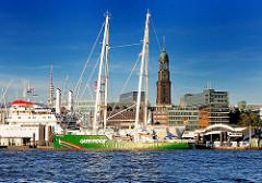 """Greenpeace Schiff """"Rainbow Warrior III"""" in Hamburger Hafen - im Hintergrund die St. Michaeliskirche."""