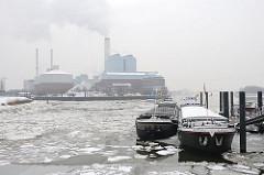 Binnenschiffe an ihrem Liegeplatz in der Billwerder Bucht - das Wasser ist mit Eisschollen bedeckt. Weisser Qualm steigt aus den Schornsteinen des Kraftwerks Tiefstack.