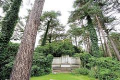 Parkfriedhof Hamburg Ohlsdorf - hohe mit Efeu bewachsene Bäume - Grabanlage mit Relief.